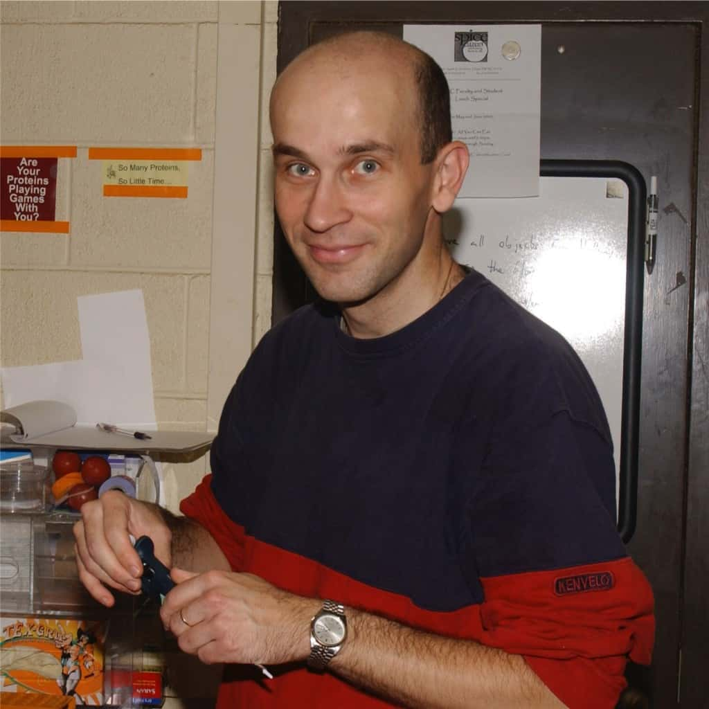 A man at a lab workstation wearing a navy and red sweatshirt. He holds a pipette in his hands.