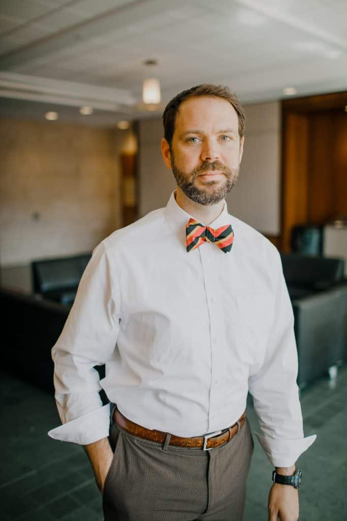 A man with short brown hair and a beard. He is wearing a white collared shirt with the sleeves turned up as the wrists and a striped bow tie with navy, orange and gold stripes.
