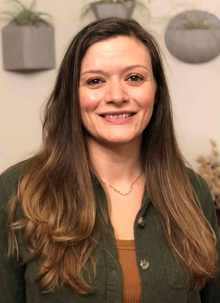 A smiling woman with long brown hair wearing a green buttoned jacket and light brown shirt underneath.