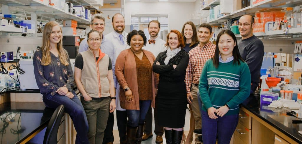 A group of eleven people smiling and standing in a research lab.