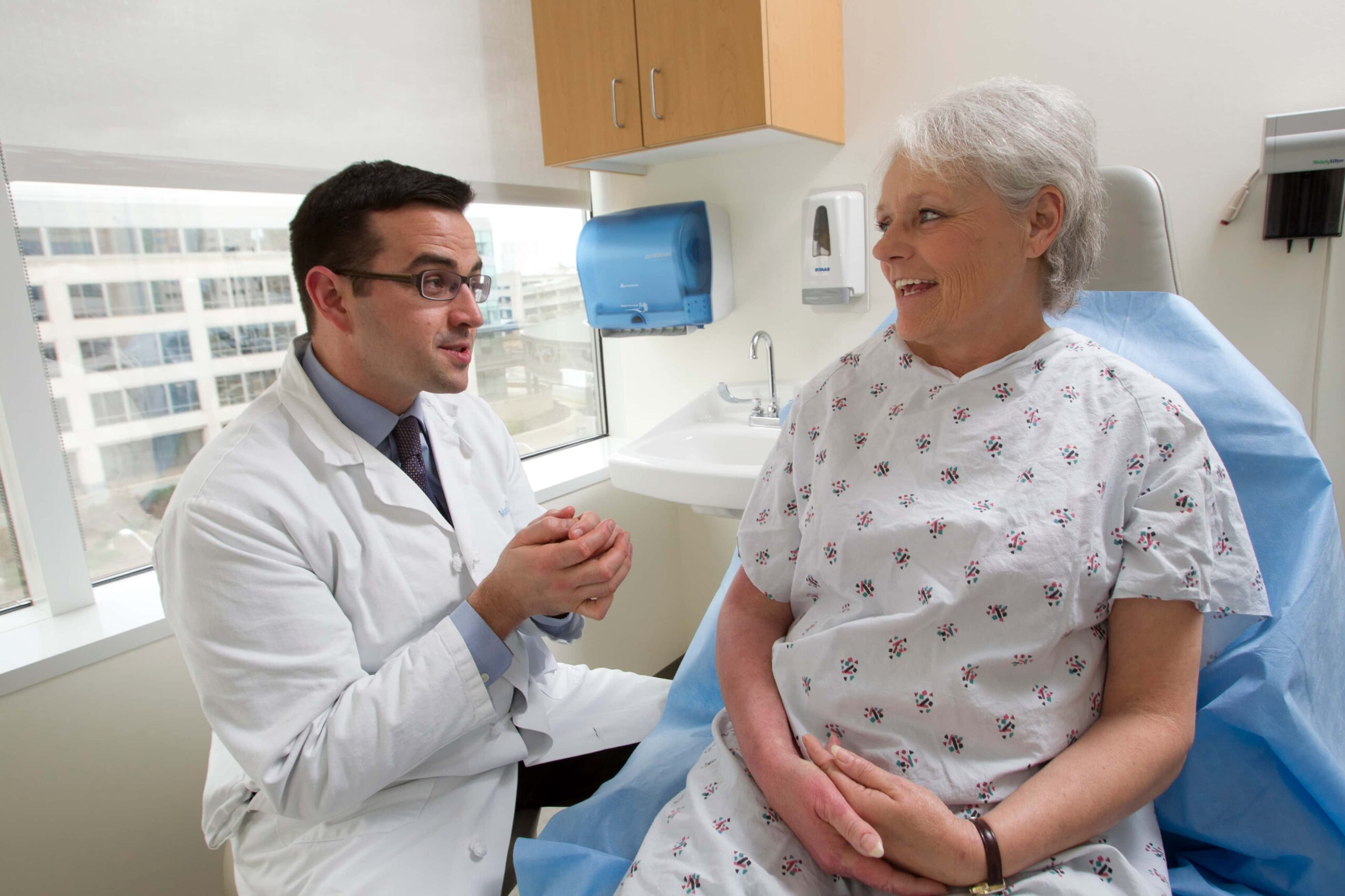 A physician talks with a patient in an exam room at the N.C. Cancer Hospital