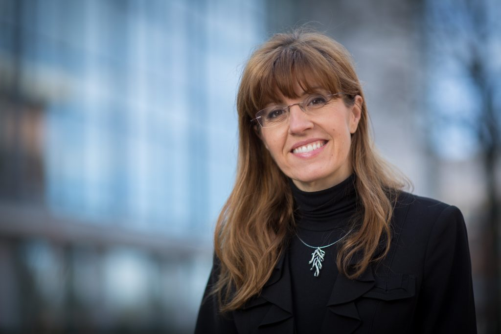 A smiling woman with long brown hair wearing glasses, a black turtleneck with a silver necklace.