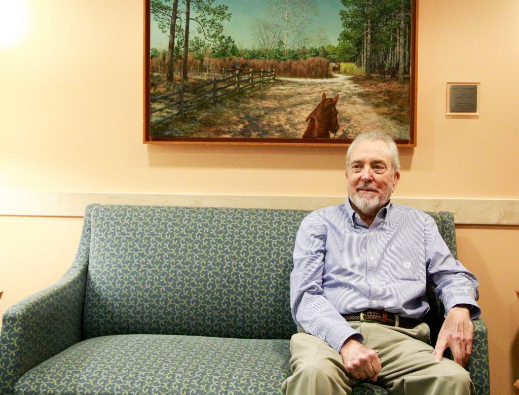 Ken Johnson sits on a green sofa in a waiting room in the N.C. Cancer Hospital