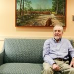 Ken Johnson sits on a green sofa in a room in the N.C. Cancer Hospital