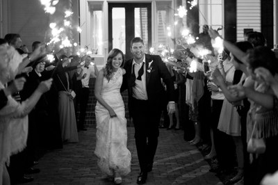 A newly-married bride and groom exit their wedding reception through a tunnel of friends and family holding sparklers.