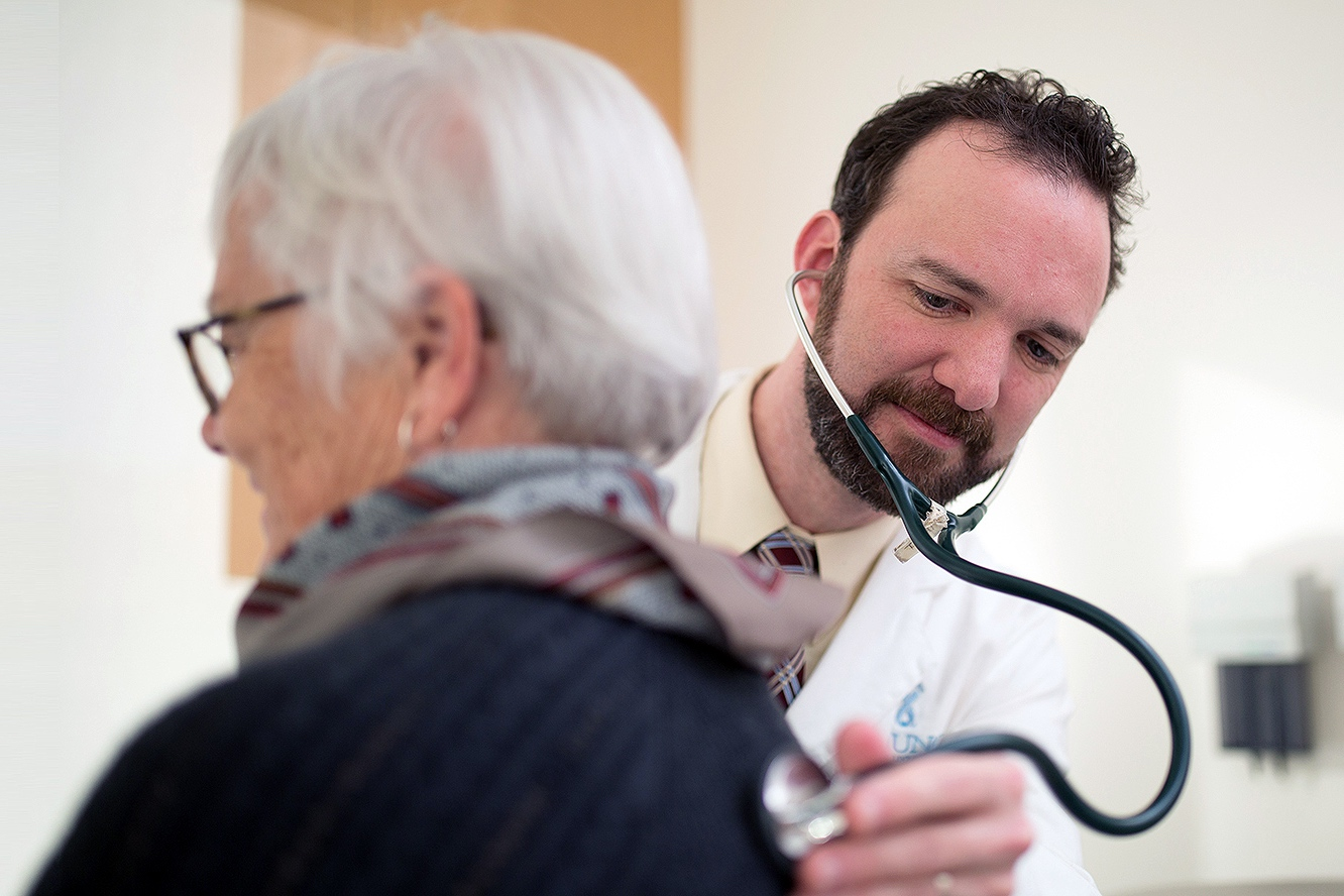 Sascha Tuchman uses a stethoscope on a patient's back