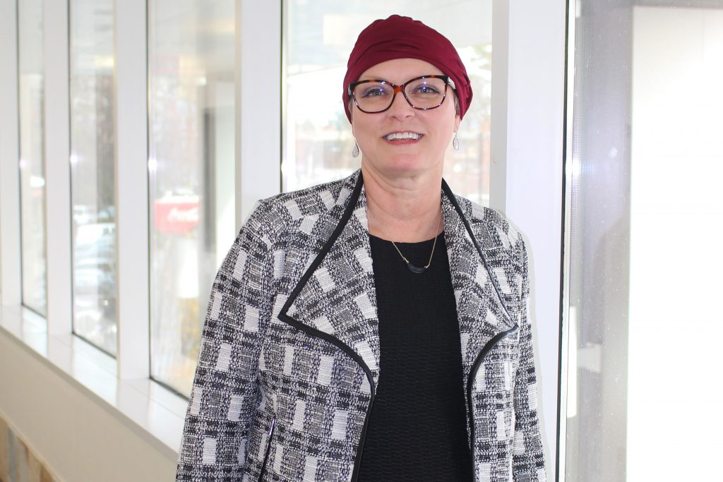 A smiling woman stands in a corridor lined with windows. She is wearing a knit red beanie hat, red glasses, and a patterned grey cardigan.