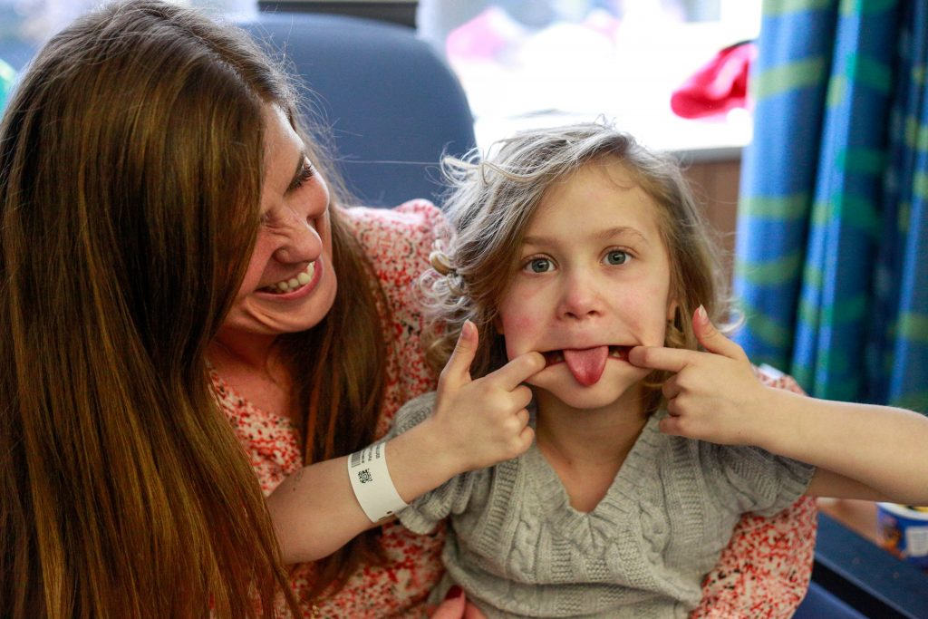 A young girl with curly blond hair makes a silly face while her mother holds her and smils.