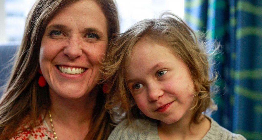 A smiling brunette woman with her daughter, a young girl with curly blonde hair.