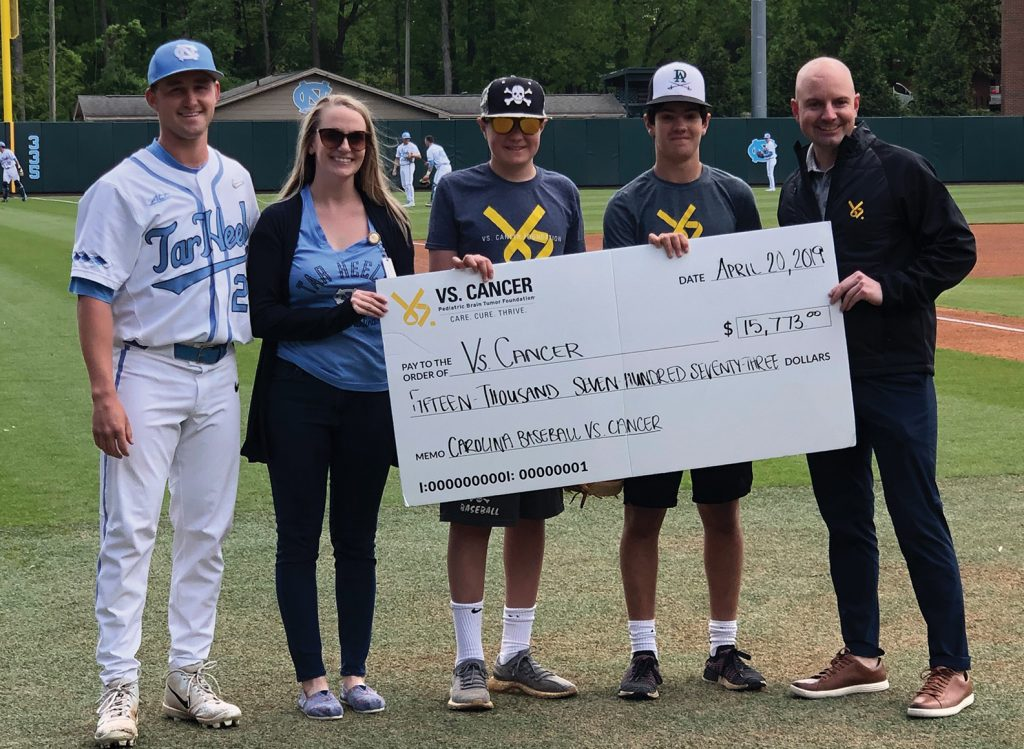 A check presentation on the UNC baseball field. Five people stand holding the check, which is made out to VS Cancer for $15,773.00. One person is a UNC baseball player wearing a uniform, one person is wearing a UNC Tar Heels shirt, and the other three people are wearing clothing with the VS Cancer organization logo.