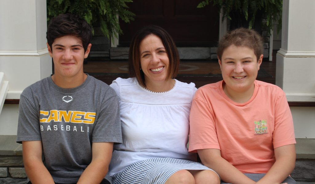 Three family members sit next to each other on the steps of their porch. The two brothers and their mom all have brown hair and are smiling.