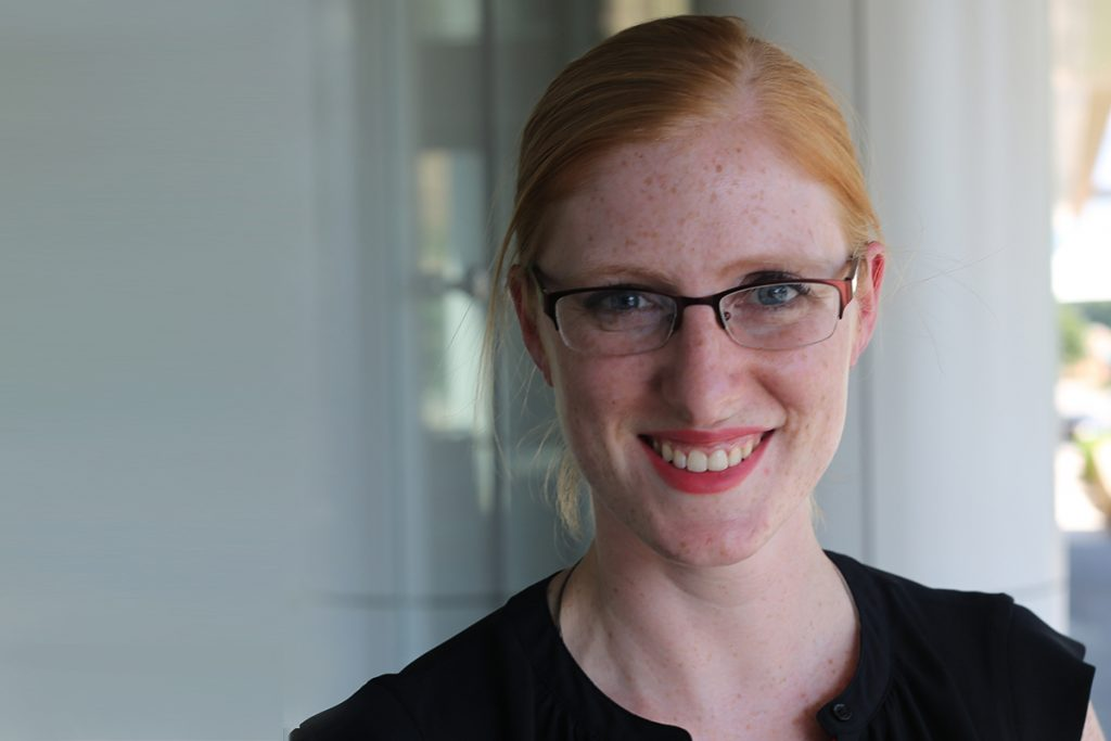 A smiling woman with orange hair pulled back wearing a black blouse, glasses and red lipstick.