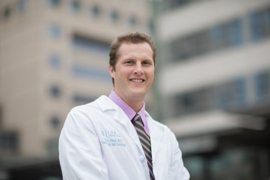 A smiling man with short blonde hair wearing a pink buttoned shirt with a striped tie and a white physicians coat. He is outside with the exterior of a healthcare building in the background.
