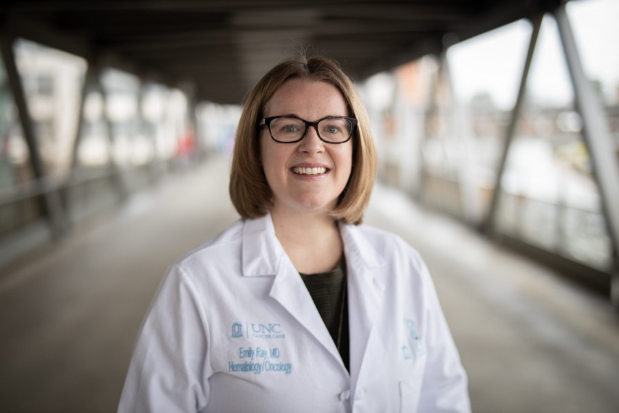 Headshot of Emily Ray on the pedestrian skywalk on the UNC Health campus in Chapel Hill.