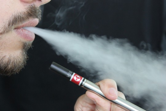 Person holding an e-cigarette and blowing smoke
