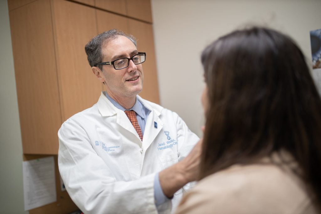 Jared Weiss wearing a doctor's white coat talking with a patient in an exam room.