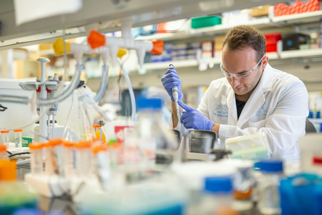 Person wearing a white coat and gloves in a research lab using a pipette.