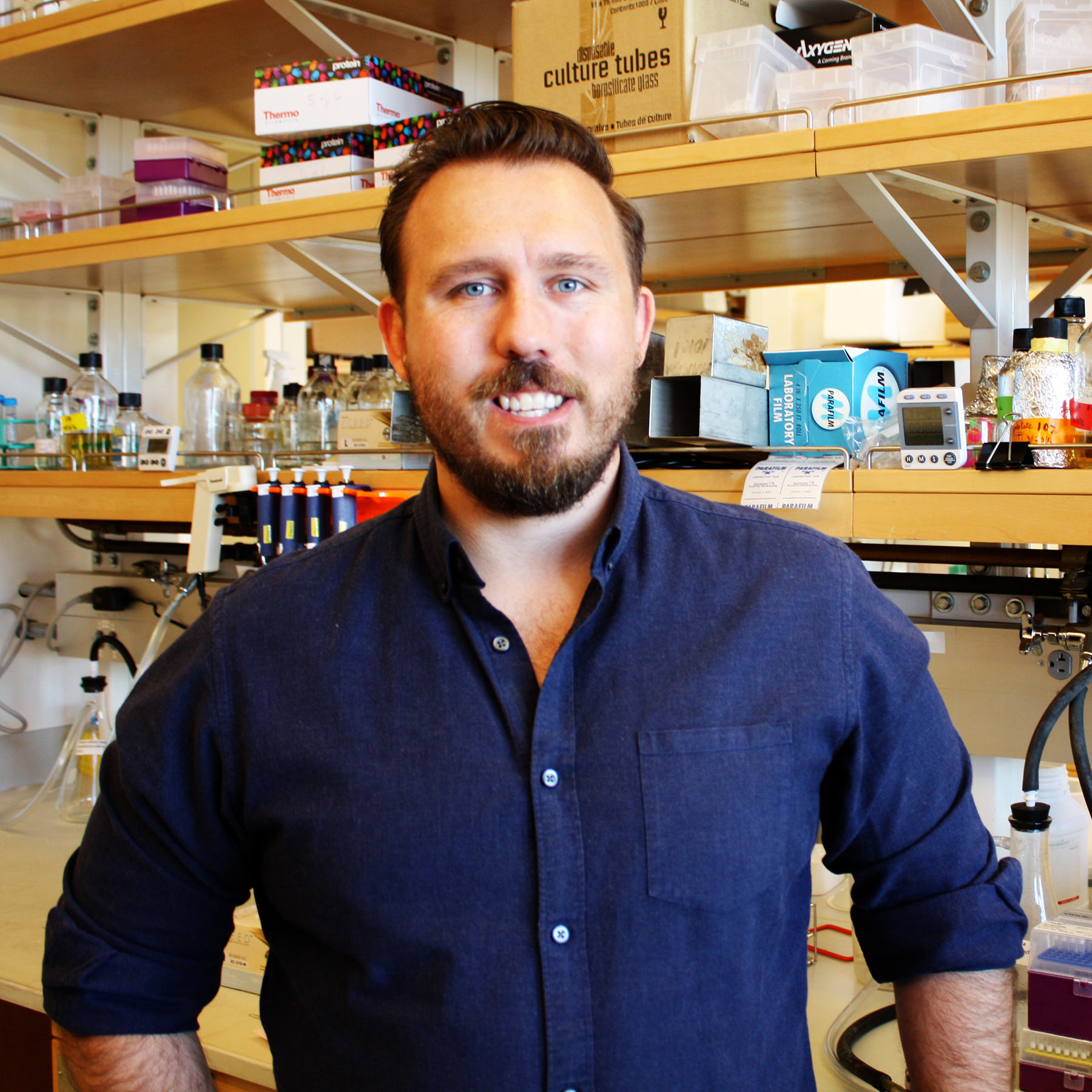 A smiling man with brown hair and a beard wearing a navy blue buttoned shirt standing in front of a lab bench with shelves full of research supplies.