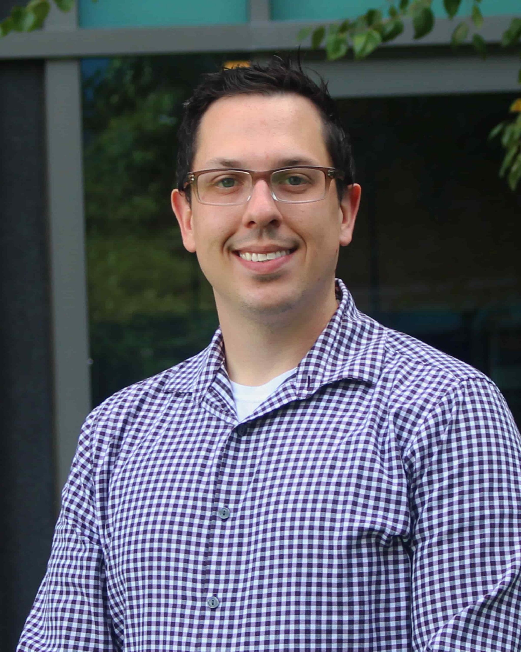 A smiling man with short dark hair wearing glasses and a blue plaid buttoned shirt.
