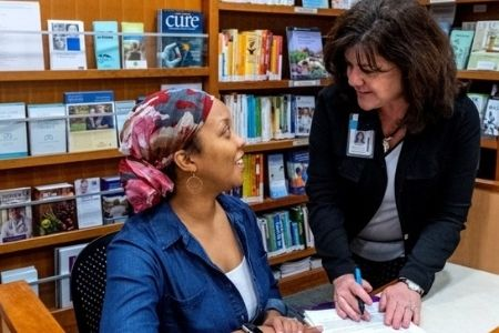 Two people at the front desk of the Patient and Family Resource Center. They are looking at each other and smiling. There are shelves of books and pamphlets behind them.