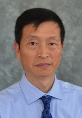 A man with short black hair wearing a light blue collared shirt with a dark blue patterned tie.