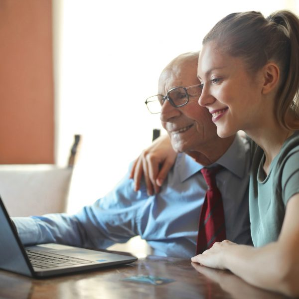 An elderly man sits at a laptop with his daughter, his caregiver. She has her arm around him and they are both smiling, looking at the laptop screen.