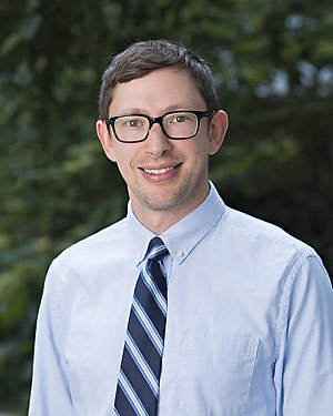 A smiling man with short brown hair wearing glasses and a light blue collared shirt with a navy and light blue striped tie.