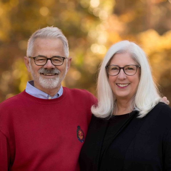 A smiling couple stands outside with an autumn background. Both people have white hair and wear glasses. They are wearing sweaters and the man has his around affectionately wrapped around the woman's shoulder.