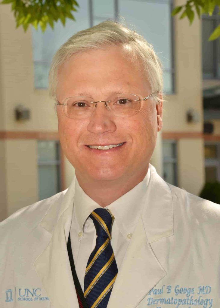 A smiling man with white hair wearing glasses, a white collared shirt and a navy tie with gold stripes. He is wearing a white physicians coat with his name embroidered, Paul B. Googe MD