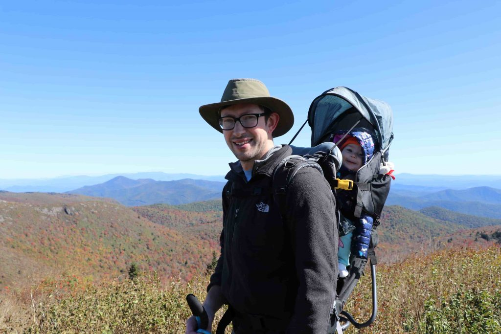 A smiling man wearing a rimmed hat stands on a mountain overlook. He is wearing glasses, a long-sleeved shirt, and is carrying a baby in a child-carrying hiking pack on his back.