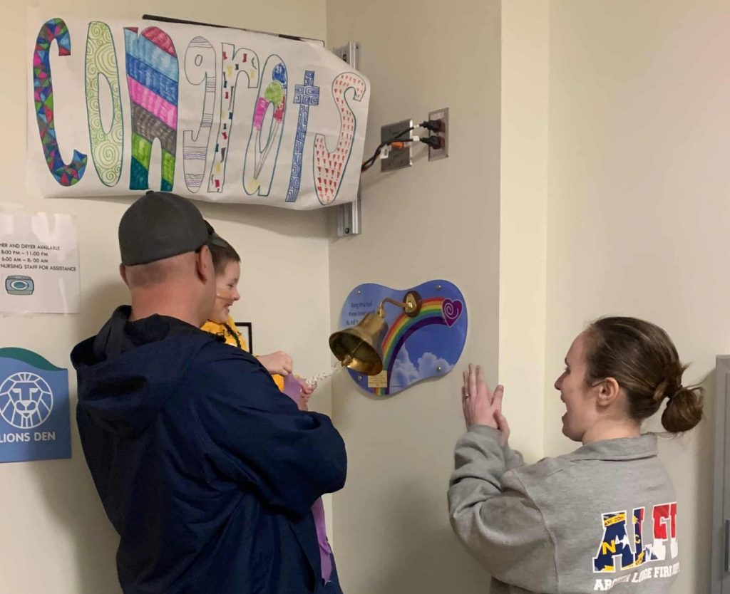 """A dad holding his young daughter while she rings a brass bell mounted to a wall. Her mom cheers alongside them, and a handmade banner with the word """"congrats"""" hangs above them."""