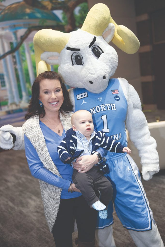 A woman holds a baby and poses with the UNC-Chapel Hill school mascot, a ram wearing a blue basketball jersey.