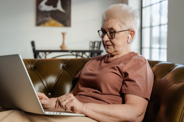 An older woman wearing glasses uses a laptop and headphones for a telehealth visit.