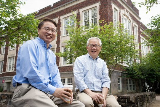 Jianping Lu and Otto Zhou sit outside of a building on the UNC-Chapel Hill campus.