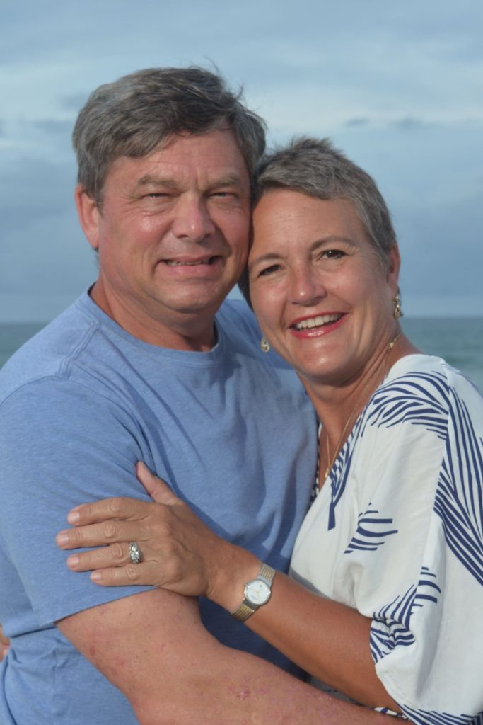 A man and a woman embrace each other in a pose on the beach.
