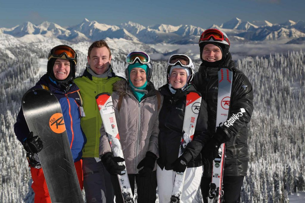 A group of smiling people stand outside with snow-covered mountains behind them. They are wearing winter sport outdoor wear and holding skiis and snowboards.