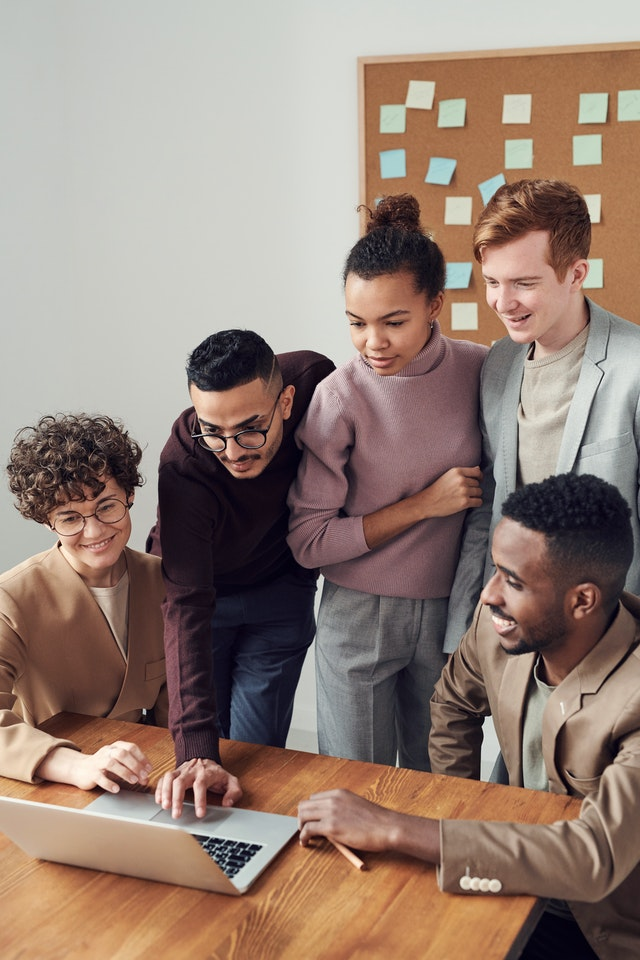 A group of people in business casual clothes gather around a laptop to collaborate.