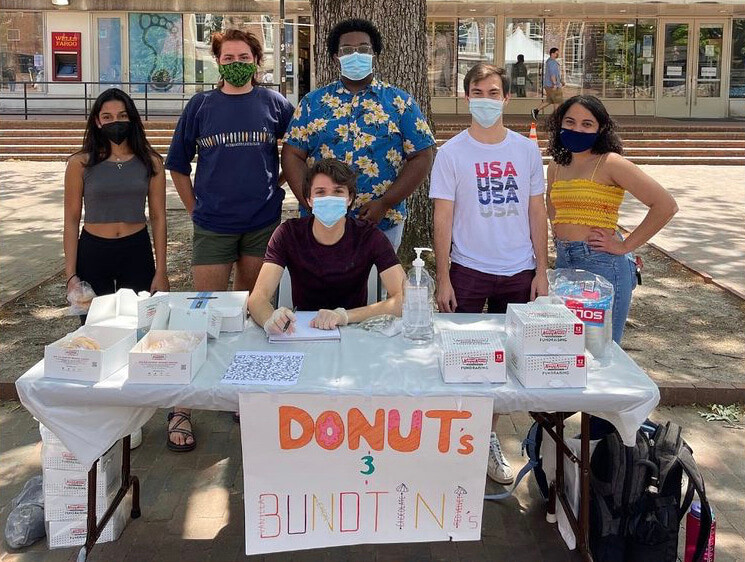 Students at a table selling baked goods for a fundraiser