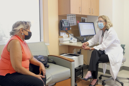 Physician-researcher Lisa Carey in the clinic with a patient