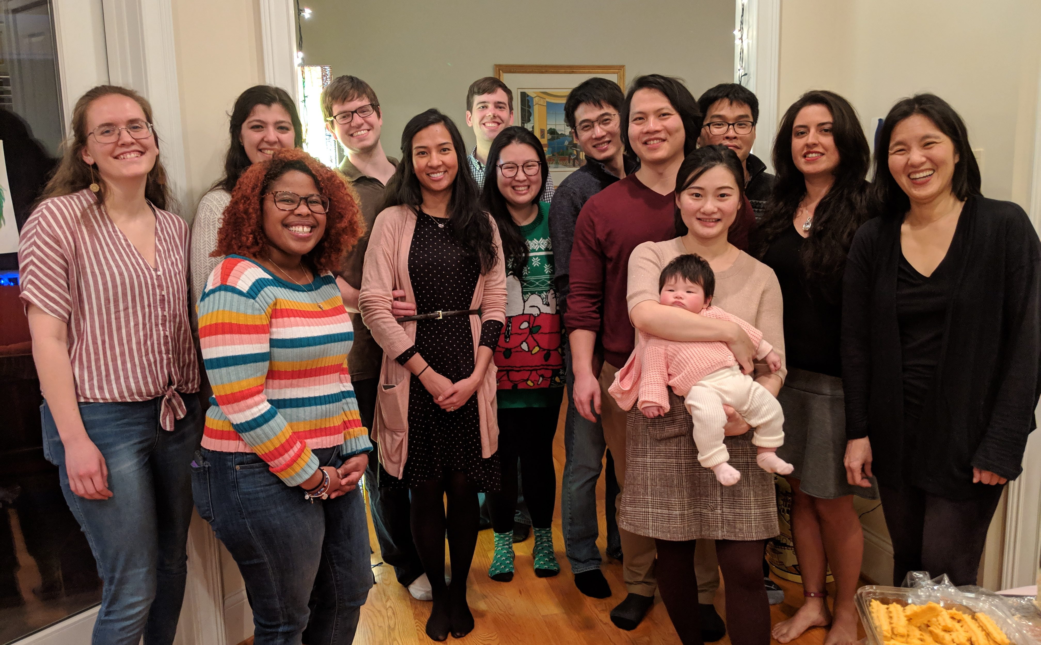 Lab Members from Yeh lab are standing together and smiling at the camera. They are dressed in warm clothes, with some holiday-themed sweaters and socks.
