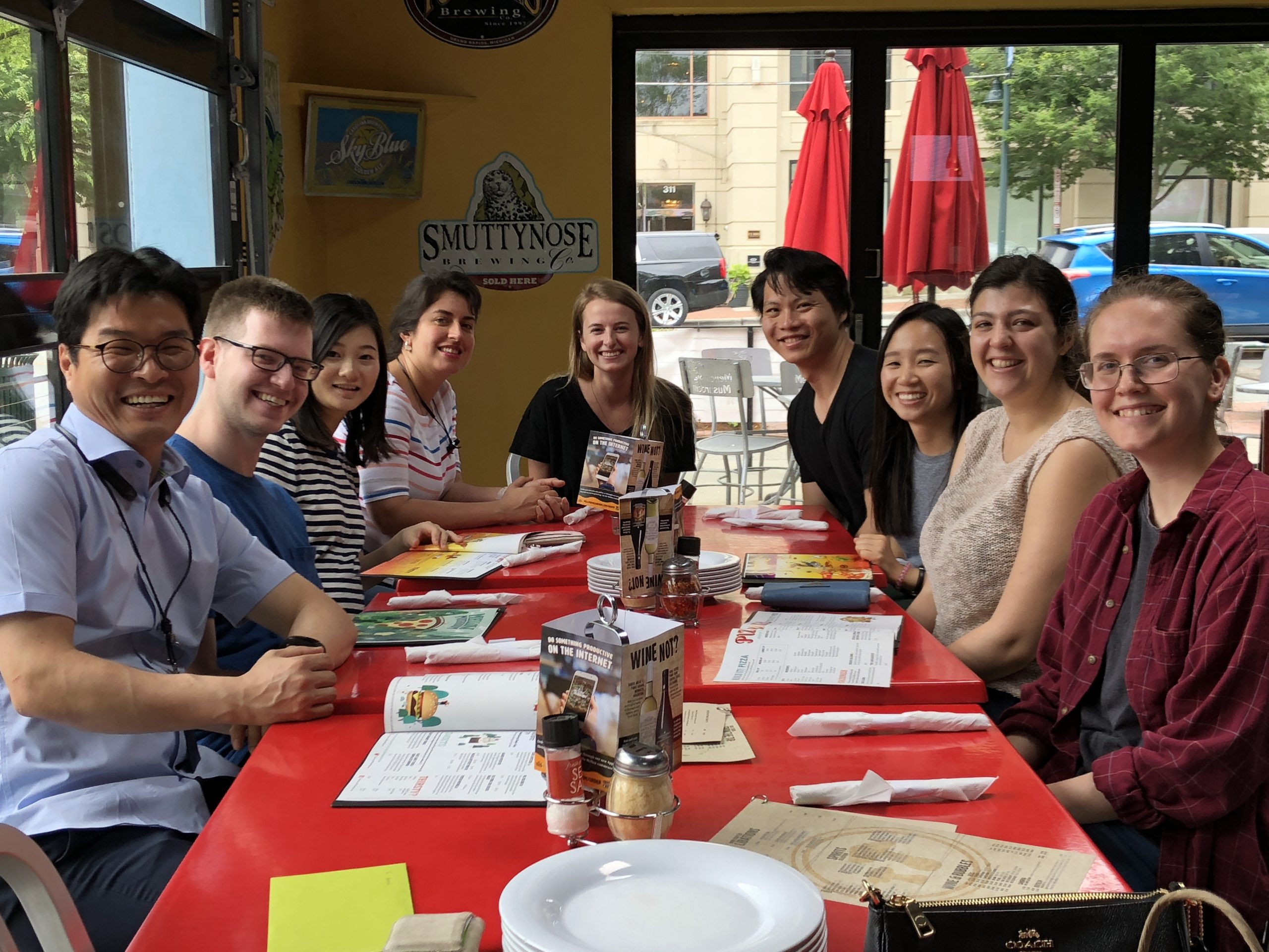 The members of Yeh Lab sitting around a table at a restaurant. They are smiling at the camera. Sarah Hennessey sits at the center, smiling.